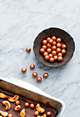 Copper-coloured chocolate balls as decoration for confectionery