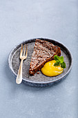 A slice of chocolate cake with fruit puree