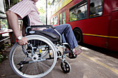 Man in a wheelchair at a bus stop