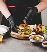 Geröstete Zwiebeln auf Cheeseburger anrichten