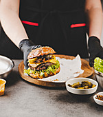 Hand holding burger with fried onions, cheese and lettuce leaf