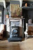 Alter Ofen vor Kaminkonsole mit Ikonenbild und Vintage-Deko