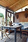 Alter Tisch und Bank auf überdachter Terrasse mit Vintage-Deko