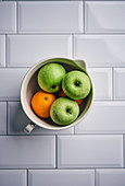 Green apples and oranges in a ceramic bowl