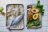 Bonito and tiger prawns on ice, with vegetables and papaya on oven trays
