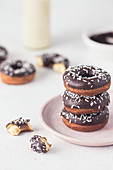 Stack of a donuts with chocolate glaze and coconut shreds