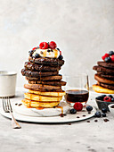 Different pancakes stacked with maple syrup and berries