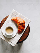 Breakfast croissant, cup of coffee and newspaper on a wooden stool