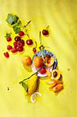 Lemons, apricots and fresh berries on a yellow background