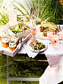 Gedeckter Tisch im sommerlichen Garten mit Hackbraten und Getränken