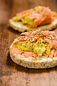 Salmon with avocado cream on rice crackers