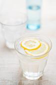 Frisches Wasser mit Eiswürfeln und Zitronenscheibe im Glas