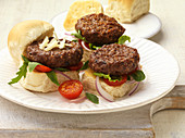 Mini burgers with a tomatoes and rocket on a plate