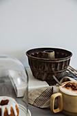 Antike Guglhupf-Backform, Cappuccino und Minikuchen unter Glashaube