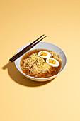 Ramen-Suppe mit weich gekochtem Ei und Essstäbchen