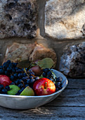 Bowl of apples with leaves and concord grapes, outside with a stone surface behind