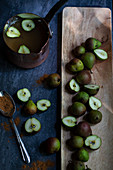 Small seckel pears, halved and whole, in a wooden tray, with a copper pot of apple cider and cinnamon