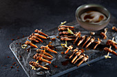Spicy grasshoppers on a skewer with chilli flakes and dip