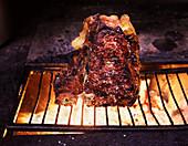 T-Bone steak grilling over olive wood
