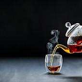 Dampfender schwarzer Tee wird aus Teekanne in Glasbecher gegosssen