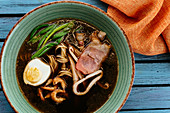 Asian noodle soup with egg and seafood