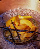 Preserves being made: apricot slices being removed from vanilla broth
