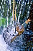 Eine Flasche Rosewein im Drahtkorb hängt in Wasserfall