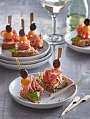 Canapés with prosciutto, melon and olives