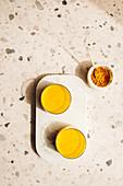 Goldene Milch daneben Schälchen mit Kurkumapulver