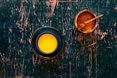 Turmeric Golden Milk on saucer and distressed green wooden surface