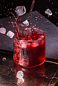 Splashing red wine with ice cubes in a glass