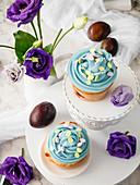 Pflaumencupcakes mit blauer Buttercreme und Mini-Zuckereiern