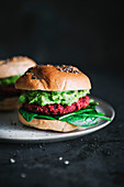 Vegetarian bagel burger with red beet patty and avocado