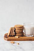 Cookies und ein Glas Milch auf Holzbrett vor hellen Hintergrund