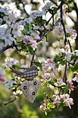 Schwälbchen und Herz aus Holz in blühendem Apfelbaum
