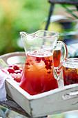 Granatapfel-Pimms in Krug und Gläsern auf Tisch im Freien