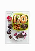 Teenager-Lunchbox mit belegtem Bagel, Getränk, Obst und Schokolade