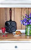 Pancake-Pfanne, Glas mit Himbeeren, Pancake-Stapel und Iris-Strauß auf Küchenablage