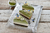 Vegan matcha vanilla cheesecake with a chocolate base and cream rosettes