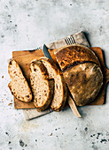 Spelt sour dough bread, sliced on a wooden board