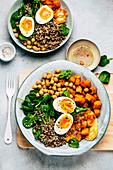 Quinoa-Bowl mit Süßkartoffeln, Kichererbsen, Spinat und gekochtem Ei