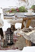 Gedeckter Tisch auf abgenutztem Teppich im winterlichen Garten
