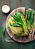 Fresh wild garlic pasta on a wooden board