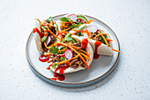 Steamed bao buns with spiced jackfruit, vegetables and siracha sauce