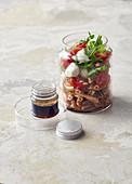 Nudelsalat im Glas mit Rucola, Mini-Mozzarella und Tomaten