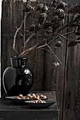 Branch of larch cones in black vase