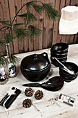 Black crockery and pine branches on table against rustic board wall