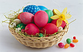 A basket of Easter eggs with a daffodil