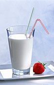 A glass of milk with two straws and a strawberry