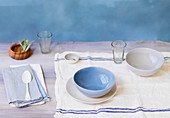 Tabletop with Napkins, Bowls, Plate and Cutlery on Tea Towel and Wood Surface